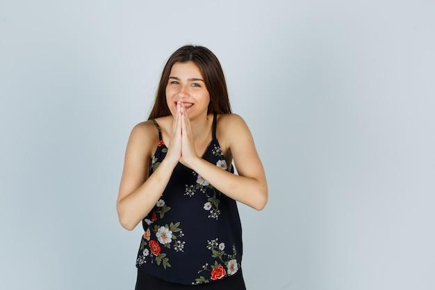 Attraktive junge dame, die namaste-geste in bluse zeigt und fröhlich aussieht, vorderansicht.