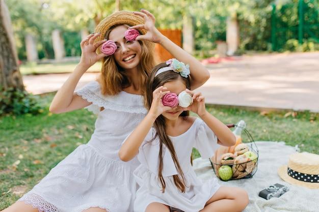 Attraktive junge dame im retro-strohhut, der mit tochter scherzt und mit bunten keksen spielt. zwei süße schwestern, die picknick im sommerpark haben und lachen.