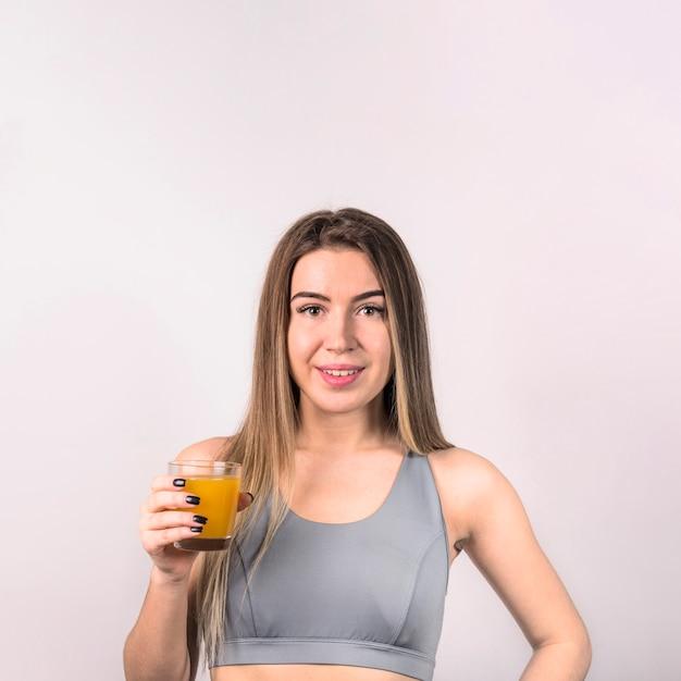 Attraktive junge dame in der sportkleidung mit glas saft