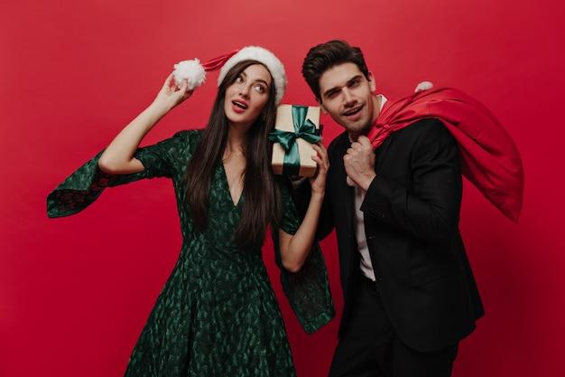 Attraktive junge dame in grünem kleid und weihnachtsmütze, die geschenkbox hält und mit hübscher brünette in schwarzem anzug posiert