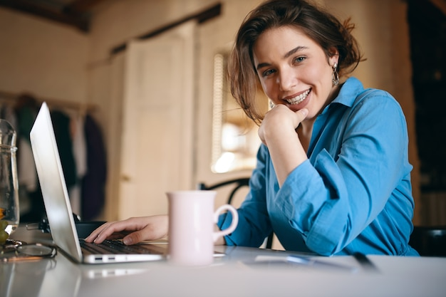 Attraktive junge designerin, die aus der ferne arbeitet und die website mit einem laptop aktualisiert.