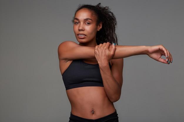 Attraktive junge dunkelhäutige lockige sportlerin mit bauchnabelpiercing, die ihre muskeln nach dem morgendlichen training im fitnessstudio streckt und im schwarzen oberteil posiert