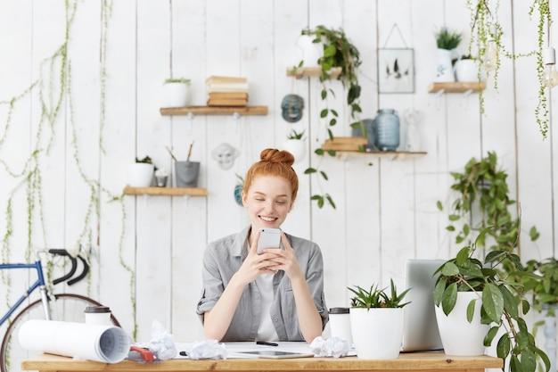 Attraktive junge europäische architektin, die ihr ingwerhaar im brötchen sitzt, das an ihrem arbeitsbereich sitzt