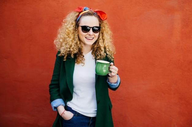 Attraktive junge europäische frau mit dem stirnband, das stilvolle jacke trägt.