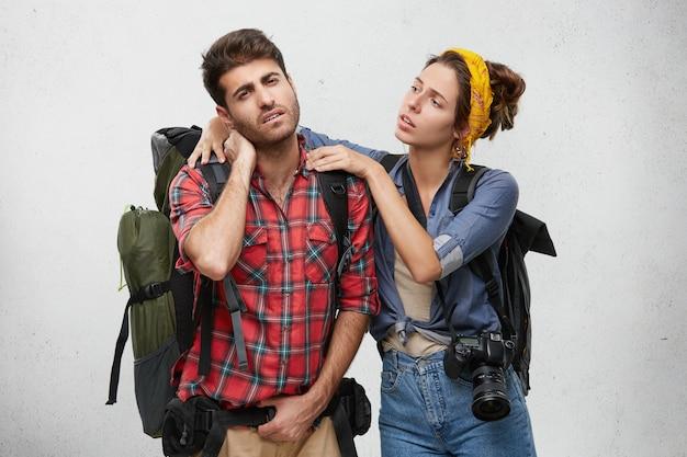 Attraktive junge europäische frau mit fotokamera, die den hals ihres frustrierten kranken freundes massiert, der nach langer harter wanderung in den bergen unter gehirnerschütterung leidet. menschen und reisen