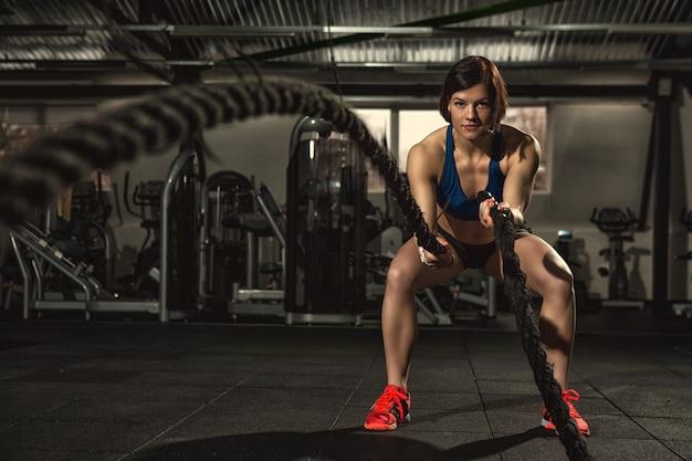Attraktive junge fit und getönte sportlerin, die im funktionellen fitnessstudio trainiert und crossfit-übungen mit kampfseilen macht