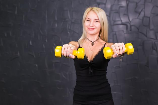 Attraktive junge fitnessfrau, die hanteln hält