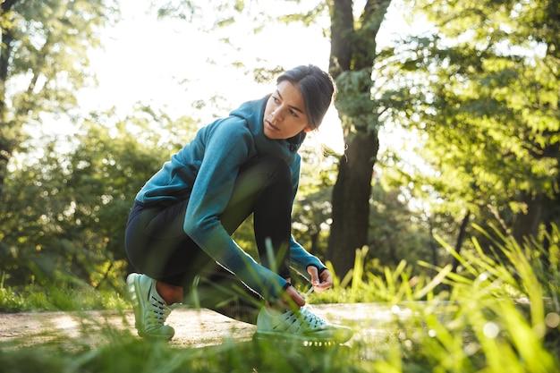 Attraktive junge fitnessfrau, die ihren schnürsenkel im freien bindet
