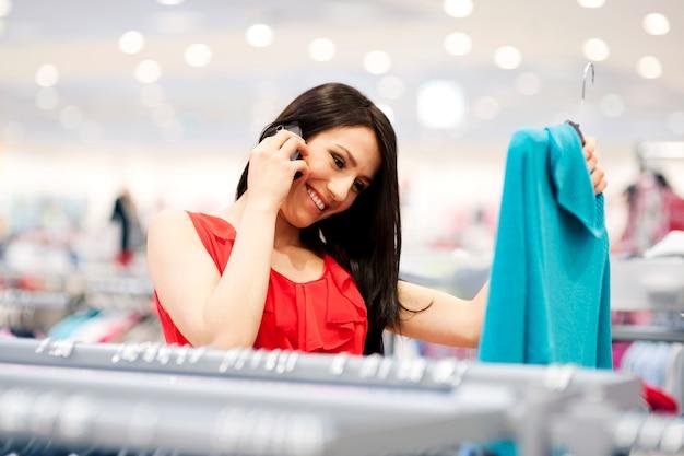 Attraktive junge frau am telefon beim einkaufen