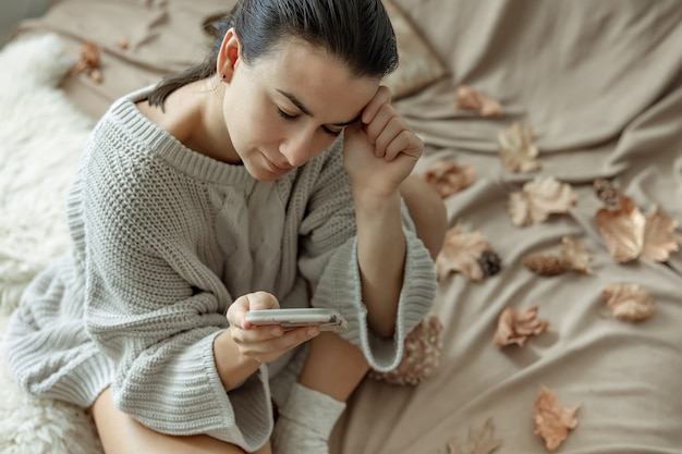 Attraktive junge frau benutzt das telefon beim sitzen im bett zwischen den herbstblättern in einem gemütlichen strickpullover.