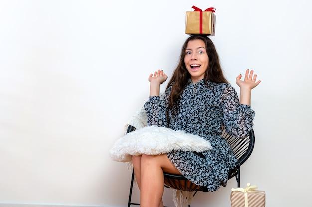 Attraktive junge frau, brünett, die auf einem stuhl sitzt und spaß mit einer geschenkbox hat, isoliert auf weißem hintergrund