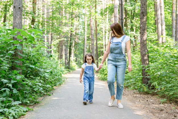 Attraktive junge frau des familiensommer- und naturkonzepts und schönes kleines tochtermädchen, das geht