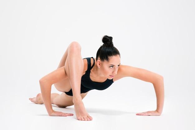 Attraktive junge frau, die akrobatischen stunt lokalisiert auf einer weißen wand tut