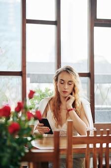 Attraktive junge frau, die am kaffeetisch sitzt und textnachrichten auf ihrem telefon überprüft