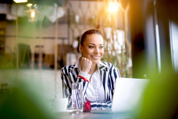 Attraktive junge frau, die am tisch mit offenem laptop sitzt