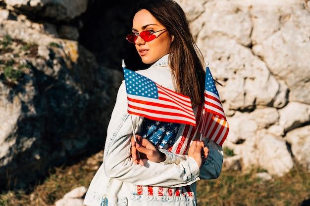 Attraktive junge frau, die amerikanische flaggen in den bergen hält