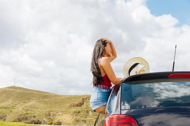 Attraktive junge frau, die auf autotür sitzt