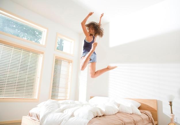 Attraktive junge frau, die auf bett springt und über schulter schaut