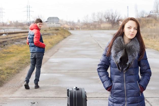 Attraktive junge frau, die auf einer landstraße auf einen aufzug wartet, mit einem gepackten koffer, der von einem jungen mann angestarrt wird, während er vorbeigeht