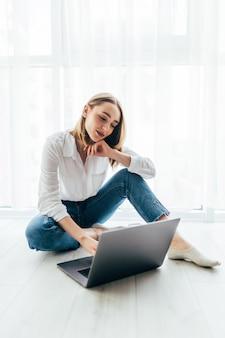 Attraktive junge frau, die auf ihrem laptop auf dem boden sitzt surft
