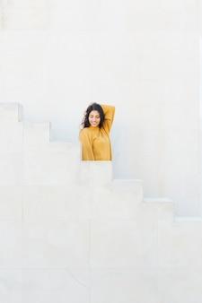 Attraktive junge frau, die auf treppenhaus steht