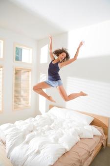 Attraktive junge frau, die ballett-art sprung auf bett tut