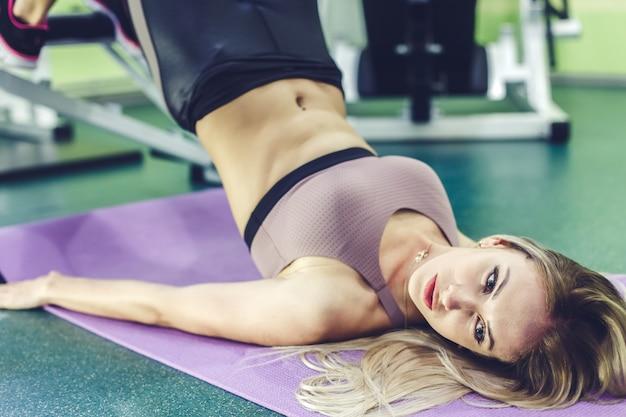 Attraktive junge frau, die bauchmuskeln in einem fitness-club pumpt.