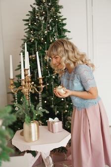 Attraktive junge frau, die beim halten einer kerze lächelt, die weihnachten feiert. silvester - gemütliches interieur