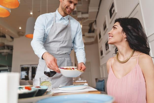 Attraktive junge frau, die caféarbeiter anschaut und lächelt, während der mann einen teller mit köstlichem salat hält?