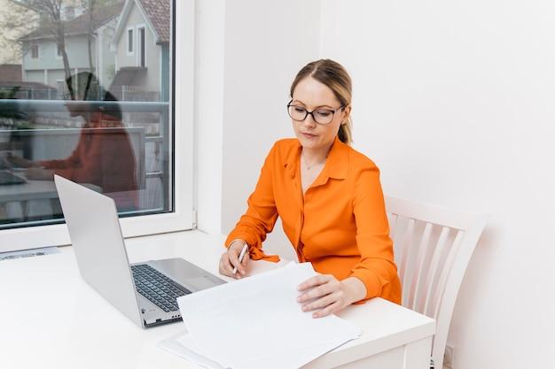 Attraktive junge frau, die dokument vor digitalem laptop sucht