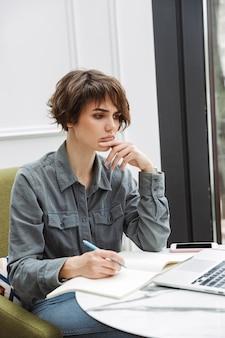 Attraktive junge frau, die drinnen am café-tisch sitzt, am laptop arbeitet und dokumente analysiert