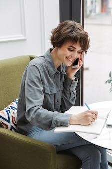 Attraktive junge frau, die drinnen am café-tisch sitzt, mit papierkram arbeitet, mit dem handy spricht