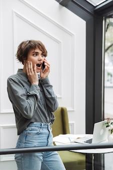 Attraktive junge frau, die drinnen im café steht und handy benutzt
