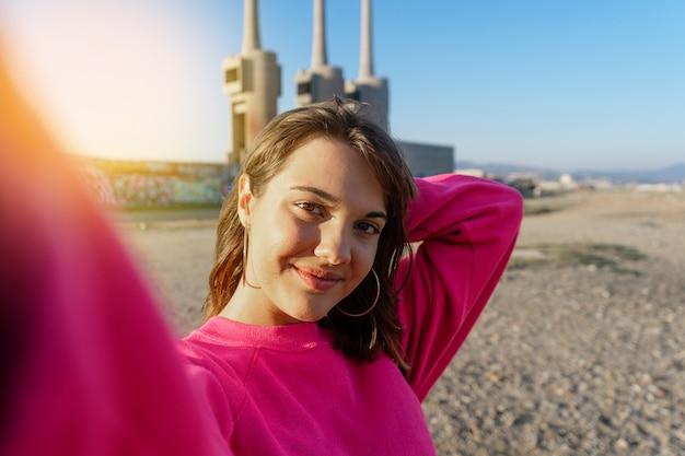 Attraktive junge frau, die ein selfie im strand nimmt
