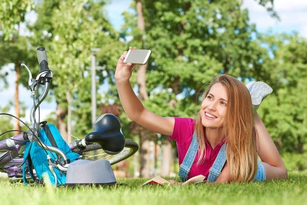 Attraktive junge frau, die ein selfie mit ihrem smartphone nimmt, während auf dem gras nahe ihrem fahrradtechnologie-gadget-mobilitätsverbindungskonnektivitäts-sozialer medienkommunikationslebensstil liegt.