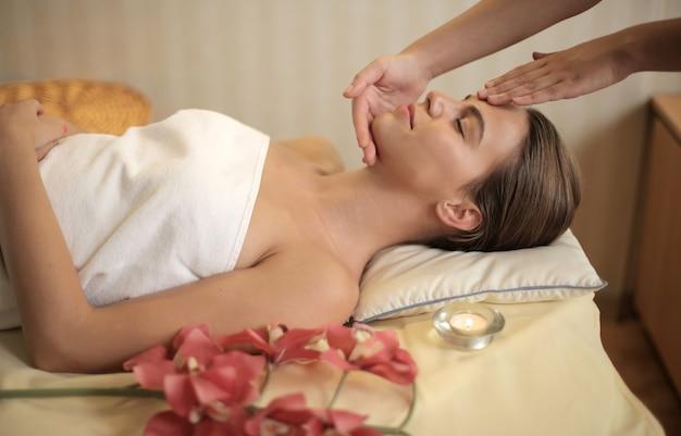 Attraktive junge frau, die eine massage in einem spa-salon bekommt