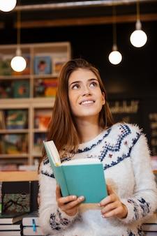 Attraktive junge frau, die eine offene buchanzeige hält und nach oben schaut, während sie in der bibliothek sitzt