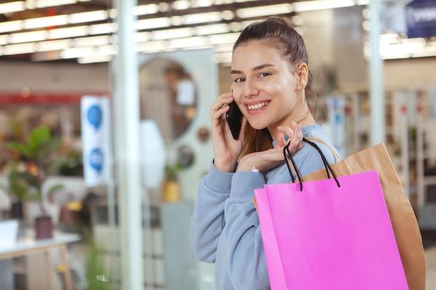 Attraktive junge frau, die einkaufstaschen im einkaufszentrum trägt, am telefon spricht, raum kopiert