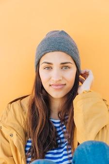 Attraktive junge frau, die gegen den einfachen gelben hintergrund trägt strickmütze sitzt