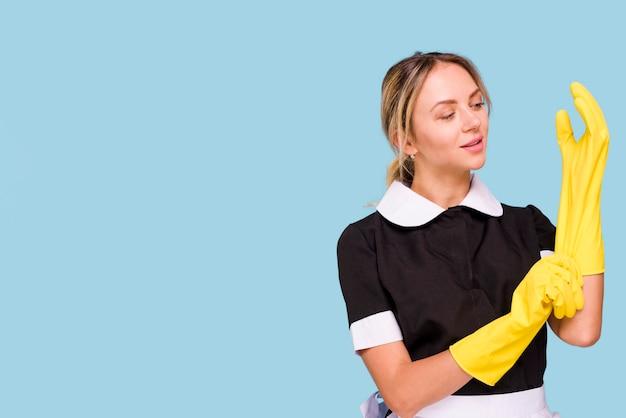 Attraktive junge frau, die gelben handschuh gegen blauen hintergrund trägt