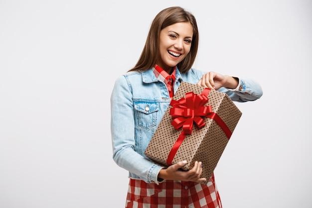 Attraktive junge frau, die geschenkbox aufdeckt, die froh und lächelnd schaut