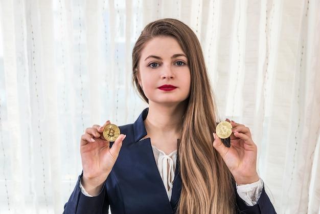 Attraktive junge frau, die goldene bitcoins, kryptowährung zeigt