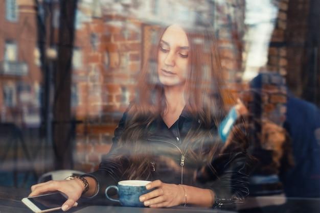 Attraktive junge frau, die handy in einem café verwendet