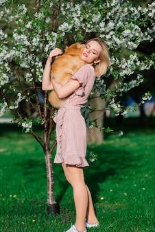 Attraktive junge frau, die hundespitz draußen hält und in die kamera lächelt, im park gehend. konzept über die freundschaft zwischen menschen und tieren.