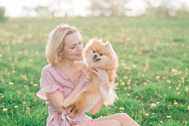 Attraktive junge frau, die hundespitz draußen hält und in die kamera lächelt, im park gehend