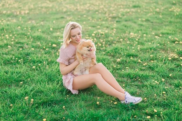 Attraktive junge frau, die hundespitz draußen hält und in die kamera lächelt, im park gehend.