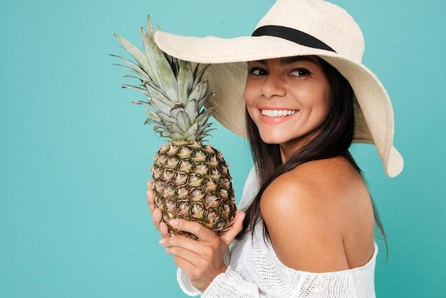Attraktive junge frau, die hut hält, der ananas hält.