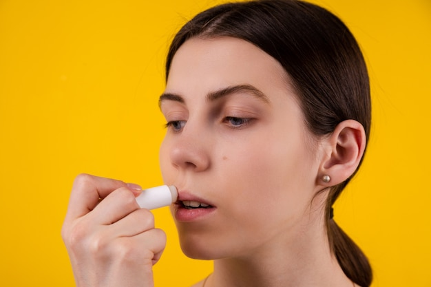 Attraktive junge frau, die hygienischen lippenstift auf gelbem hintergrund verwendet. lippenpflege und schutz.