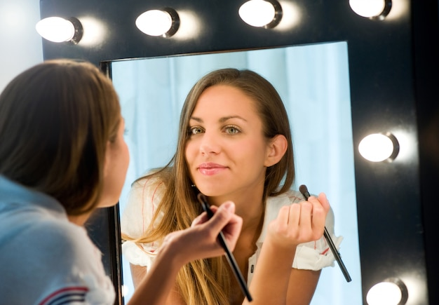 Attraktive junge frau, die ihr make-up anwendet