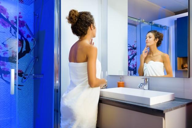 Attraktive junge frau, die ihr spiegelbild im badezimmerspiegel bewundert, während sie in ein sauberes weißes handtuch eingewickelt wird, nachdem sie in einem persönlichen hygiene- und schönheitskonzept geduscht hat